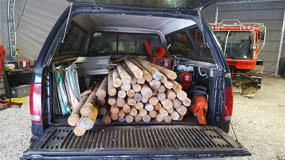 Pickup truck bed loaded with sign posts and trail maintenance supplies