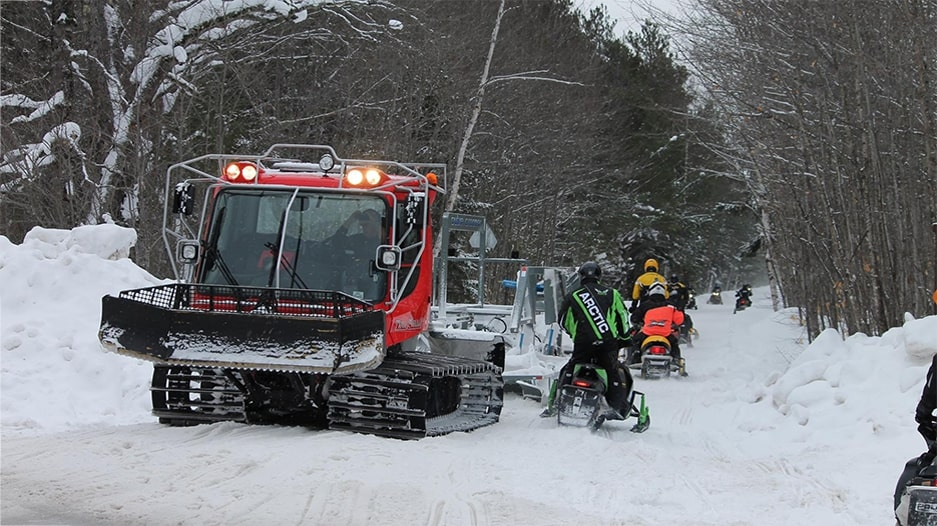 Pisten Bully groomer and passing snowmobiles
