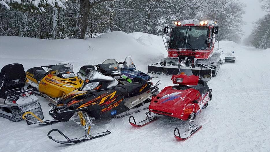Pisten Bully groomer with snowmobiles