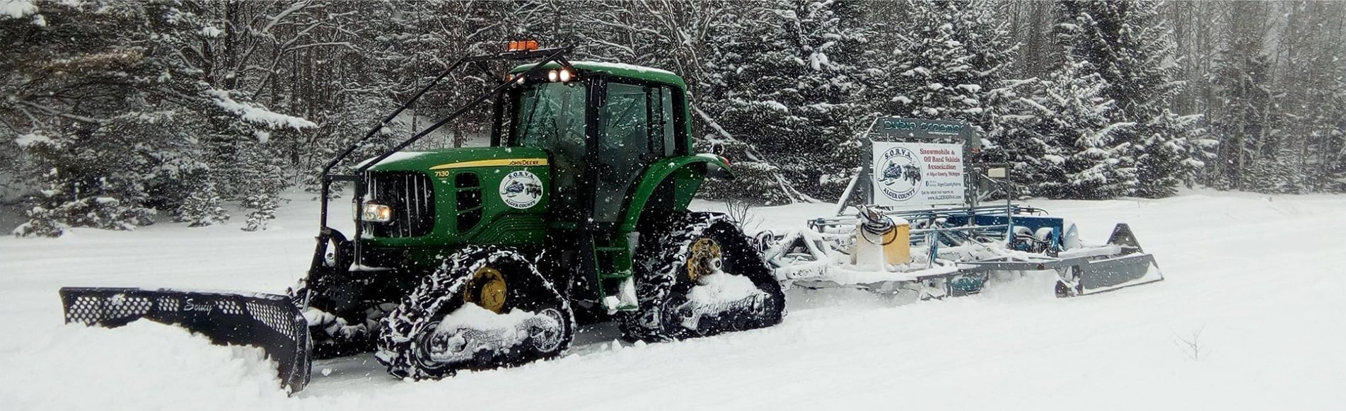 Deere tractor in the snow with groomer